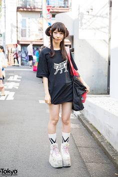 20-year-old Asahi on the street in Harajuku wearing a skeleton cat print t-shirt from the Japanese brand Undercover with shorts and tall Buffalo platform shoes.