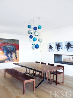 The dining room features a raw-edged walnut table with a cast-bronze base from BDDW ; the chandelier is by Bocci. The bull painting is by Joseph Adolphe and the palm trees are by Karin Dauch.