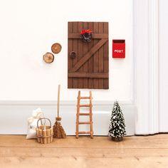Nissedør i brunt træ med dørkrans og masser af tilbehør. Denne nissedør ligner en brun stalddør og har følgende tilbehør: Spand, stige, kost, postkasse, melsæk, juletræ og knager. Med denne nissedør er du og ungerne klar