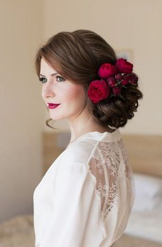 Romantic red flower hairpiece low curly updo wedding hairstyle; Featured: Elstile