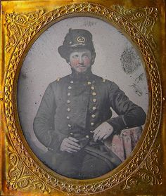 """Sixth plate soft emulsion ambrotype of a Virginia officer attributed to the """"Hanover Troop"""". He sits here dressed in a minty double breasted frock which appears to be loosely based off of US regulation dress. Most likely an early war image. His coat still relatively new as it shines in the sunlight. Atop his head is worn is worn a M1851 Hardee hat with an ostrich plume. His hat badge prominently displays """"VA"""" encircled within a wreath."""