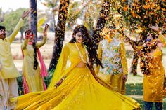 Flower shower on haldi | Twirling bride | Indian wedding rituals | Bride to be in Mustard Yellow lehenga for her haldi ceremony | Indian Wedding Photography | Candid Shot | Indian bridesmaids | Flower jewelry | Image source: Wedmegood | Every Indian bride's Fav. Wedding E-magazine to read.Here for any marriage advice you need | www.wittyvows.com shares things no one tells brides, covers real weddings, ideas, inspirations, design trends and the right vendors, candid photographers etc.