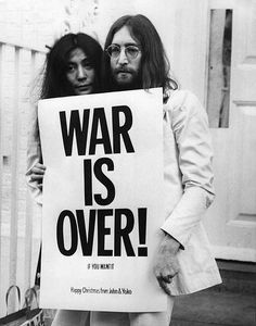 John Lennon and Yoko Ono pose on the steps of the Apple building in London, holding one of the posters that they distributed to the world's major cities as part of a peace campaign protesting against the Vietnam War. 'War Is Over!, If You Want It'. 1st December, 1969.