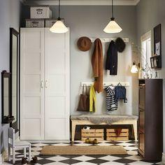Eteinen, jossa valkoinen vaatekaappi, ruskea kenkäkaappi, massiivimäntyinen penkki ja kaksi valkoista naulakkoa.