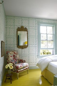 A lively guest room features a yellow floor and China Seas' Lyford Trellis wallpaper in an upbeat mix of mint green and white.