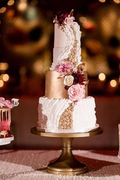 Stunning white and gold wedding cake with pink and red flowers; Featured Photographer: Ashley Fisher Photography, Featured Cake: Sugarbelle Cakery