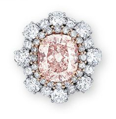 A colored diamond and diamond ring - Set with a cushion-shaped fancy brownish orangy pink diamond weighing 3.03 carats, within a row of light pink diamonds, to the brilliant-cut diamond undulating surround and pavé-set diamond gallery extending to the three quarter-hoop, mounted in 18k white and rose gold, ring size 3. (I would rather like to imagine this as a beautiful brooch design)