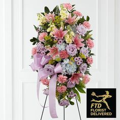 Honor someone who was a true light in your life with a gorgeous display of lavender roses and button poms, pink Asiatic lilies and carnations, yellow stock, blue hydrangea, solidago and vibrant greenery with a lavender ribbon on a wire easel. Present this arrangement at the funeral or memorial to not only pay your respects, but also offer solace to others mourning a person who will be truly missed. Bouquet sizes are approximate.<br><br>Handmade & Delivered by Your FTD Florist....