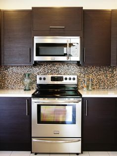 Multicolored mosaic tiles are used as the backsplash to make a statement in this contemporary kitchen. Tones of bronze, gold and brown highlight the dark wood cabinets, stainless steel appliances and white stone countertops.