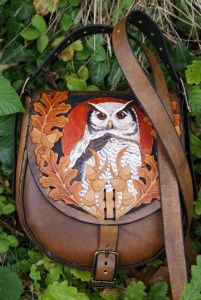 elaborately carved brown leather bag with owl and wolf amidst oak leaves
