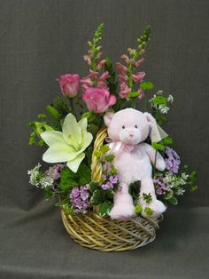 Basket of flowers with a teddy bear for a new baby in the house.