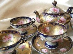 Cups, saucers and teapots - blue, gold and pink roses. <3