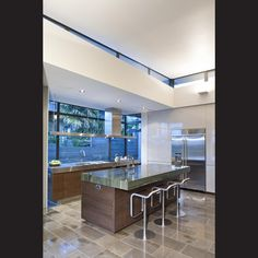 Solid natural surfaces and gleaming stainless steel in this kitchen continue the interior aesthetic of the whole house.