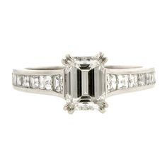 Emerald Cut Engagement Ring:: centering an Emerald cut diamond weighing app. 1.23ct. (E color, VVS2 clarity), flanked by fourteen mixed cut diamonds weighing app. 1.00ctw., fashioned in platinum. Contemporary. Size 6 GIA 2141502421