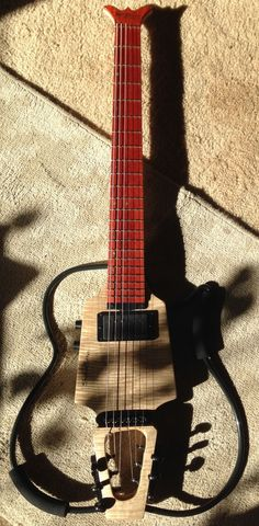 SoloEtte Jazz travel guitar. Figured maple body with a Padauk fingerboard. Picture was taken in the sunshine with lovely shadows. Gorgeous!