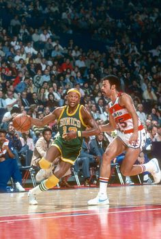 Slick Watts of the Seattle Supersonics drives on Phil Chenier of the Washington Bullets during an NBA basketball game circa 1975 at the Capital...