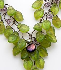 Green Statement Necklace featuring leaves cascading over one another as they dangle from the vine offset with amethyst Swarovski crystals.