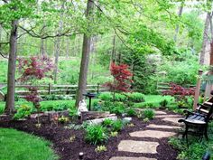A beautiful, shady backyard with a large central bark planting bed running along the center. Along the back of the property is a split rail fence, which marks the boundary without obscuring the view of the woods and hills beyond.