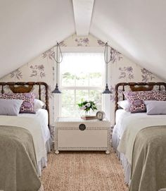 This space's striking architecture is worth embracing with the right accents. Floral wallpaper highlights a peaked roof and compliment vibrantly hued pillow shams from Garnet Hill. Opting for hanging lamps with thrift-store shades save on much-needed space on a desirable antique white nail-edge trunk.