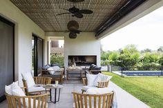 En la galería de una casa, parrilla acompañada por juego de mesa y bancos de madera. Además, dos ventiladores de ratán y lámparas colgantes. En el sector del living al aire libre, sillones en petiribí.