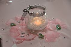 wedding center piece. A dollar tree store glass with some glitter confetti on the bottom. a candle from the dollar tree. black ribbon around the top and rose peddles around the vase and glass rocks and fake diamonds around the base. It was inexpensive and beautiful.