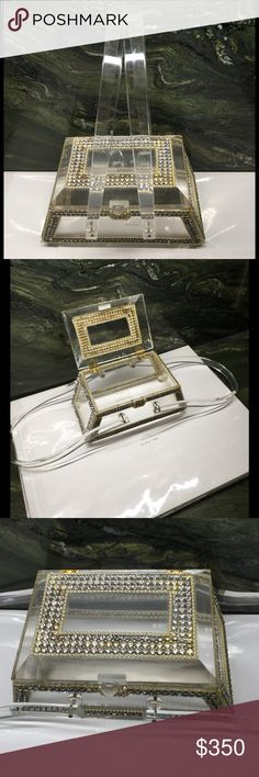 """One Of A Kind Vintage Lucite Purse. This gorgeous vintage lucite purse is for that very special occasion. Crafted by the artist Robert W. Hallman of California in the early 1950's. This is one of a kind. The top, and all 4 sides are adorned with fashioned jewels. Every jewel is intact. Brass hardware, hinged double handles. Completely clear. Measures 7"""" across the bottom, 5 1/2"""" across the top, 3 1/2"""" tall, 4"""" wide. Robert W. Hallman of California Bags"""
