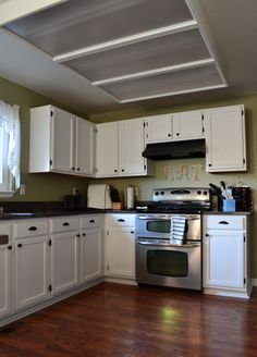 Detailed tutorial on how to paint your oak kitchen cabinets white, as well as spray painting brass hinges oil rubbed bronze to match new hardware DIY
