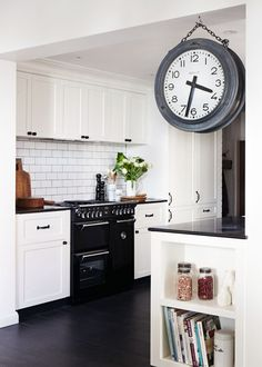 black range, floors, countertops, & hardware with white cabinets