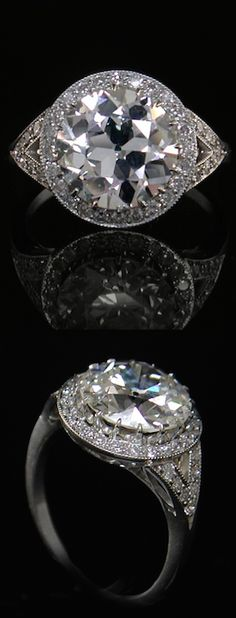 1930's vintage diamond ring; central diamond is an old European-cut solitaire; setting has sixteen small claws securing the main diamond within a halo of 24 small brilliant cut diamonds; the split shoulders are highlighted with 14 small brilliant cut diamonds; platinum.