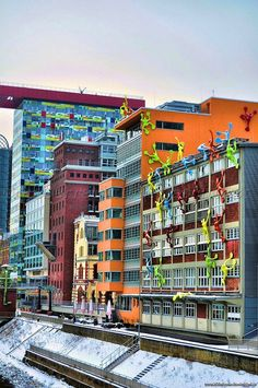 The Roggendorf House covered by climbing figures called 'Flossis' by German artist Rosalie in Duesseldorf, Germany