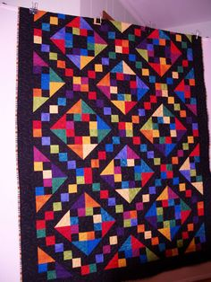 "Jimmy's Ladder.  Jacob's Ladder nap-size quilt with brights on a black background. The thread is King Tut ""Joseph's Coat."" We used the same thread top and bobbin.  The backing fabric is from Exclusively Quilters and Favorite Fabrics."