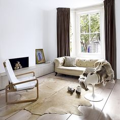 White living room with wood flooring, animal hide rug, neutral sofa and white chair