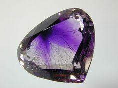 "Hematite ""Ribbons"" trapped inside a facetted amethyst."