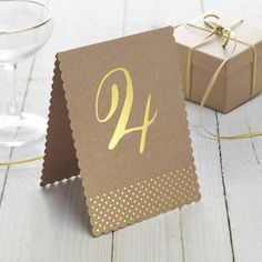 A pack of 12, brown Kraft and gold foiled wedding Table Numbers from One-Twelve. Use these table numbers to make your guest tables stand out on your big day. Each number uses kraft card with gold foiled numbers and polka dot design. Table numbers 1-12 are included in the pack. Each table number is 11cm W x 15.5cm H. Fabulous for a wedding with a rustic theme and as they are free-standing they do not need a table number holder so they are obvious but unobtrusive. Kraft Card 12cm x 18cm x...