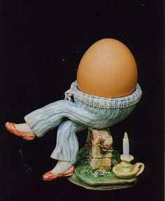 """Humpty Dumpty egg cup."" Excuse me, but *why* is there a candle under his butt? I don't remember *that* as part of the Humpty tragedy. I find this egg cup altogether creepy. Reminds me of Dr. Seuss's ""pair of pale-green pants with nobody inside them."""