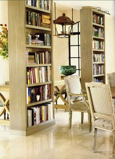 Love the floating bookcases. I've done this. Bookcases are a great room divider. Always love bookcases in a dining space.