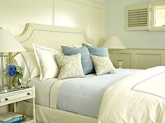 Creamy white wainscoting, painted shutters, sumptuous linens, and an upholstered headboard make this Southampton master bedroom luxurious.