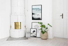 Collage med tavlor i ett vardagsrum. Snygg vit inredning. Tavla med berg och skog. Poster med citat.