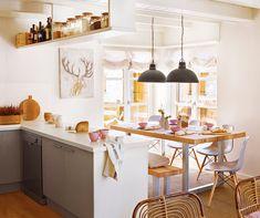 Cocina comedor en tonos blancos y tostados con vajilla en rosa. En el comedor