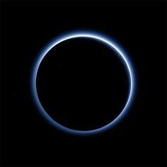 太陽を背にした冥王星。大気が青く光っている。画像処理で肉眼で見たときの色に近づけたという=NASA