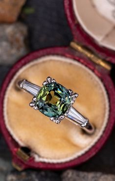 This gorgeous green sapphire engagement ring features a 2.63 carat no heat sapphire with Madagascar origin that we sourced and set in a 1960s platinum diamond mounting. The shoulders are each channel set with one (1) tapered baguette cut diamond.