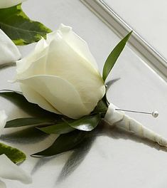 The FTD® White Rose Boutonniere creates the classic picture of elegance. A single white rose is chosen for its absolute perfection, then accented with lush greens and a white satin ribbon to offer its