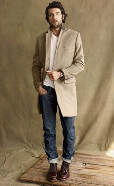 camel overcoat over white tee and washed denim, with brownish-oxblood boots