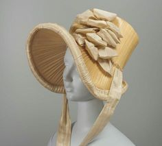 Woven straw bonnet trimmed with cream silk taffeta ribbon and plaited straw. French, about 1815 - in the Museum of Fine Arts Boston.
