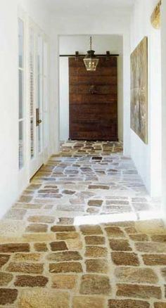 Chateau Domingue-Provence style hallway with foyer pendant lighting and wooden sliding door with natural stone flooring. Via Cote de Texas. Future House, My House, Floor Design, House Design, Deco Champetre, Faux Stone, Stone Flooring, Modern Flooring, Flooring Ideas