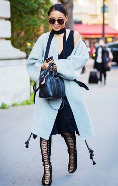 Margaret Zhang wears a knee-length dress, wool coat, skinny scarf, lace-up boots, and a Givenchy bag