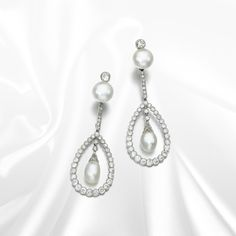 Pair of natural pearl and diamond pendant earrings. These swing-set pendant earrings feature natural pearls and circular- and single-cut diamonds.