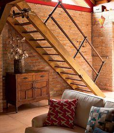 No projeto da arquiteta Kita Flórido, o espaço debaixo da escada que leva ao mezanino foi usado para colocar um aparador. Como a casa é pequena, não há lugar para muitos móveis, então cada cantinho foi aproveitado para caber tudo