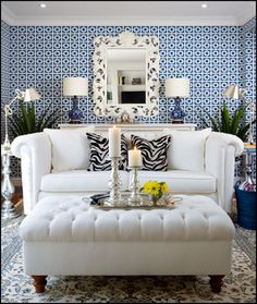 Love the graphic wall paper paired with the white couch.  The tufted ottoman and the zebra print pillows...gorgeous!!