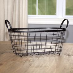 "Black Wire Storage Basket: The industrial-style wire basket is great for decorating your home or organizing anything from toys to linens. Crafted from sturdy iron wire in a black finish, this basket has large handles for easy carrying.  - Dimensions: 17.25""L x 10.75""W x 10.25""H"